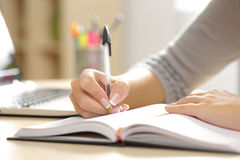 Woman hand writing in an agenda at home. Close up of a woman hand writing in an agenda on a desk at home or office Stock Image