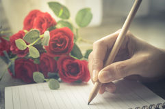 Woman hand writing on book with rose. Vintage filtered Royalty Free Stock Photography