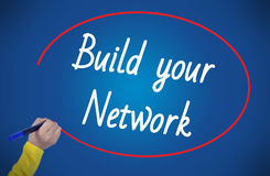 Woman hand writing build your network with marker. On blue background professionally Stock Photos