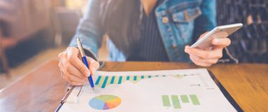 Woman hand writing on charts and graphs that show results with a stock photography