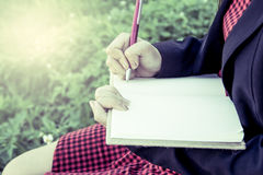 Woman hand writing her notebook in the garden. Vintage filter Royalty Free Stock Image