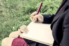 Woman hand writing her notebook in the garden Royalty Free Stock Photography
