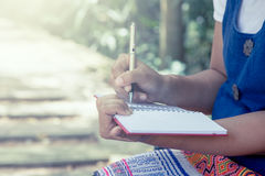 Woman hand writing on her notebook in the park. Vintage filter Royalty Free Stock Photo