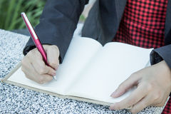 Woman hand writing her notebook. On table Royalty Free Stock Image