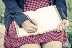 Woman hand writing her notebook. Vintage filter Stock Photos