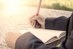 Woman hand writing her notebook. Vintage filter Royalty Free Stock Image