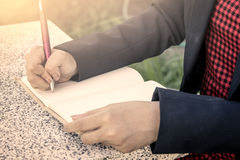 Woman hand writing her notebook. Vintage filter Royalty Free Stock Photo