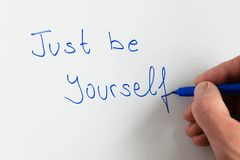 Woman hand writing the motivational phrase `Just be yourself`. On white background royalty free stock photos