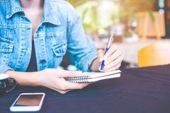 Woman hand is writing on a note pad with a pen in the office. stock photos