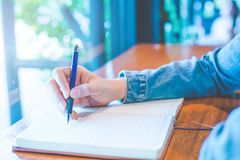 Woman hand is writing on a note pad with a pen in the office. Woman hand is writing on a note pad with a pen in the office Royalty Free Stock Image