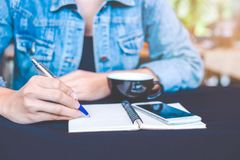 Woman hand is writing on a note pad with a pen in the office. Stock Photo