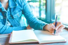 Woman hand is writing on a note pad with a pen in the office. Woman hand is writing on a note pad with a pen in the office Royalty Free Stock Photography