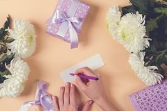 Woman hand writing a note with the text thank you on a pape Stock Photos