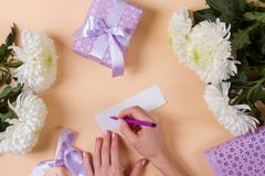 Woman hand writing a note with the text thank you on a pape Royalty Free Stock Images