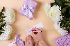 Woman hand writing a note with the text thank you on a pape Stock Image