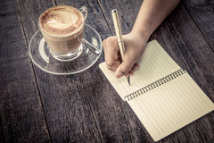 Woman hand writing on notebook over wooden table Stock Images