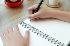 Woman hand writing on notebook paper with a pen on wooden desk i. N cafe Royalty Free Stock Photo