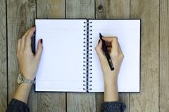 Woman hand writing on notebook with pen. royalty free stock photography