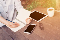 Woman hand writing notebook and phone, tablet on table in garden Stock Photo