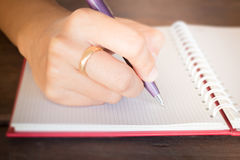 Woman hand writing on noteboook paper Royalty Free Stock Images