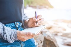 Woman hand writing on a notepad with a pen at the beach. Royalty Free Stock Photography