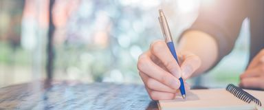 Woman hand writing on a notepad with a pen in the office. Web banner stock photos