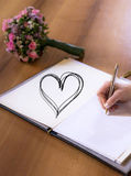 Woman hand writing with pen in book with heart textspace copyspace wedding flower bouquet. Woman hand writing with pen in a book with heart textspace copyspace Stock Photo