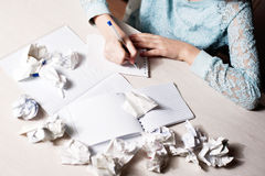 Woman hand writing with pen on notebook.there are crumpled paper Royalty Free Stock Image
