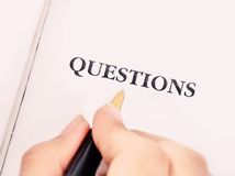 Woman hand with writing questions Royalty Free Stock Image