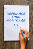 Woman hand writing refinance your mortgage on math book. With marker Stock Image