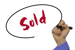 Woman Hand Writing Sold on blank transparent board with a marker Stock Image