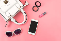Woman handbag with makeup and accessories isolated on pink backg Stock Photos