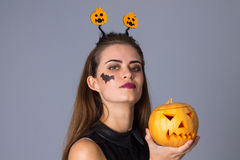 Woman with handband holding a pumpkin Stock Photos