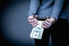 Woman handcuffed for her crimes with US Dollars in her hands as. Symbol of corruption and bribe stock image