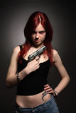 Woman with handgun. Young redhead holding a gun across her chest Royalty Free Stock Images