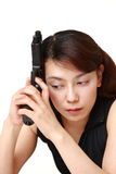 Woman with a handgun thinks. Studio shot of young Asian woman on white background stock image
