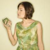 Woman with handheld radio. Pretty Caucasian mid-adult woman wearing green vintage dress looking at handheld radio Stock Photos