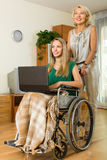 Woman and handicapped girl with laptop Royalty Free Stock Photography