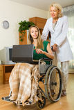 Woman and handicapped girl with laptop Stock Photos