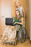 Woman and handicapped girl with laptop Stock Photo