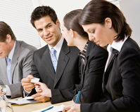 Woman handing co-worker business card. In meeting in conference room Stock Image