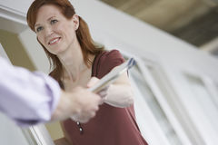 Woman Handing Colleague Document. Closeup of a smiling women handing colleague document in office Royalty Free Stock Photo