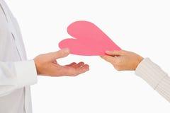 Woman handing man a paper heart Stock Photo