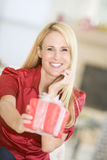 Woman Handing Out Christmas Present royalty free stock photo