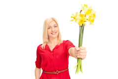 Woman handing out flowers towards the camera Royalty Free Stock Photo