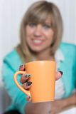 Woman is handing over a cup of coffee Royalty Free Stock Images