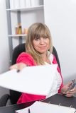 Woman is handing over a document Stock Photography