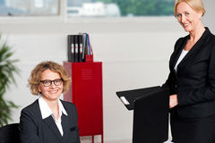 Woman handing over files to her female boss Royalty Free Stock Image