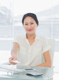Woman handing over her business card at desk Royalty Free Stock Photography