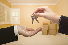 Woman Handing Over the House Keys Inside Empty Room Royalty Free Stock Photo